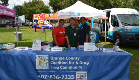 Three OC employees working a booth at Health Summit