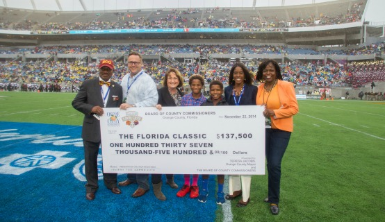 Mayor Jacobs and personnel with a check to the Florida Classic
