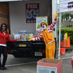 Ronald McDonald and a Good Day Orlando representative with toys for toy drive