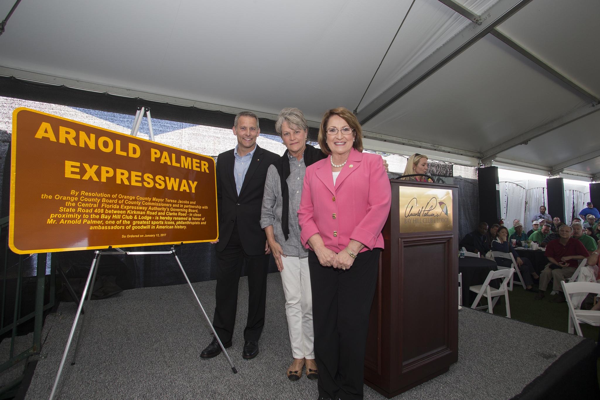 """La Alcaldesa Jacobs junto a dos personas en la presentación del cartel de señalización de la autopista """"Arnold Palmer Expressway"""""""