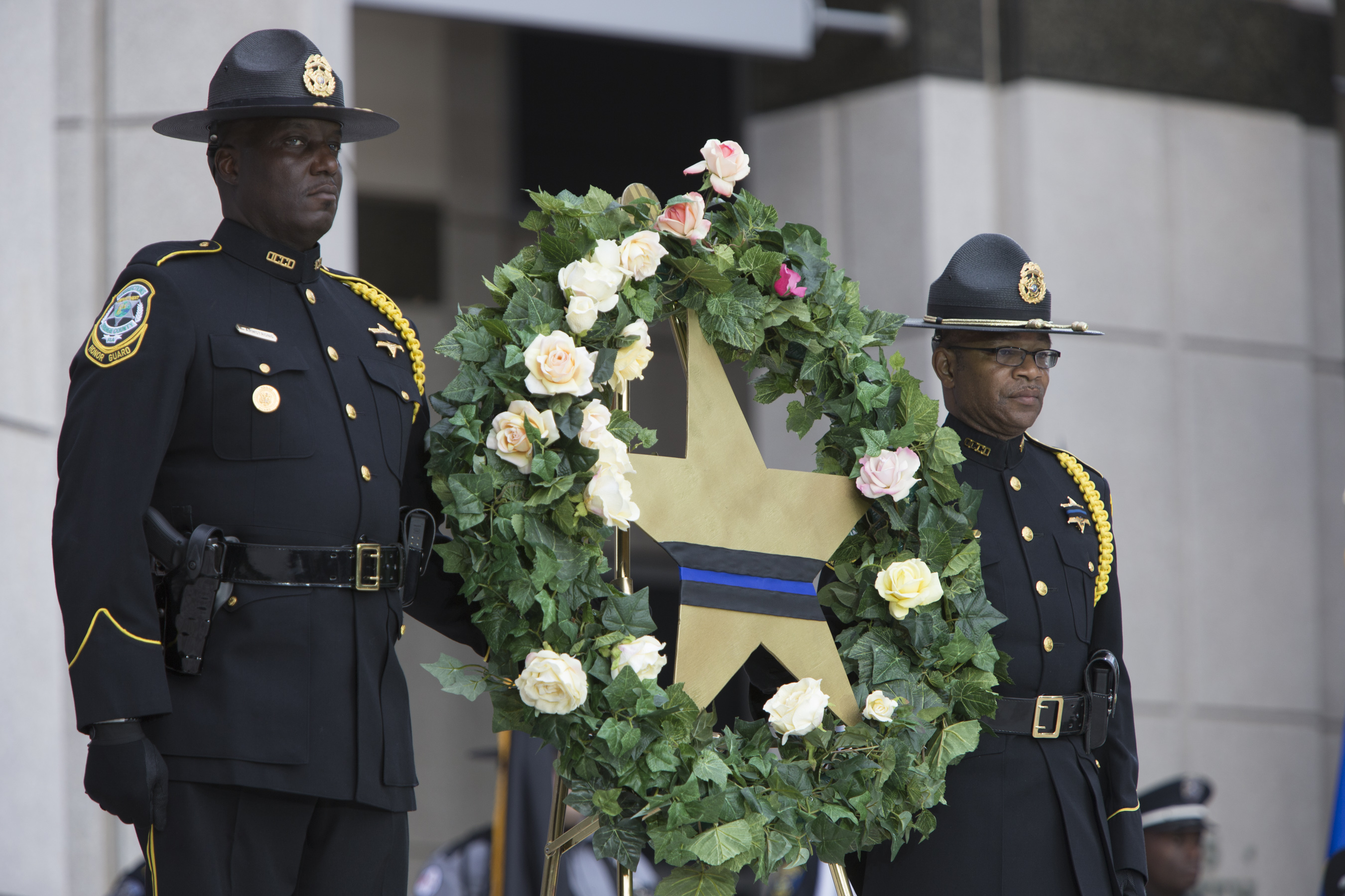 Two law enforcement officers carrying a wreath