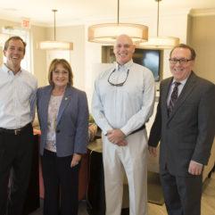 La Alcaldesa Jacobs junto a tres personas en un nuevo Complejo de Apartamentos Asequibles