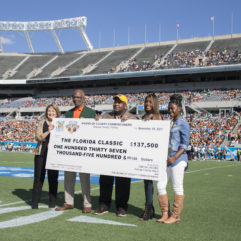 Mayor Jacobs is stainding on the field of a stadium holding a large check with four other people.