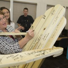 Mayor Jacobs signing wooden rocking chair