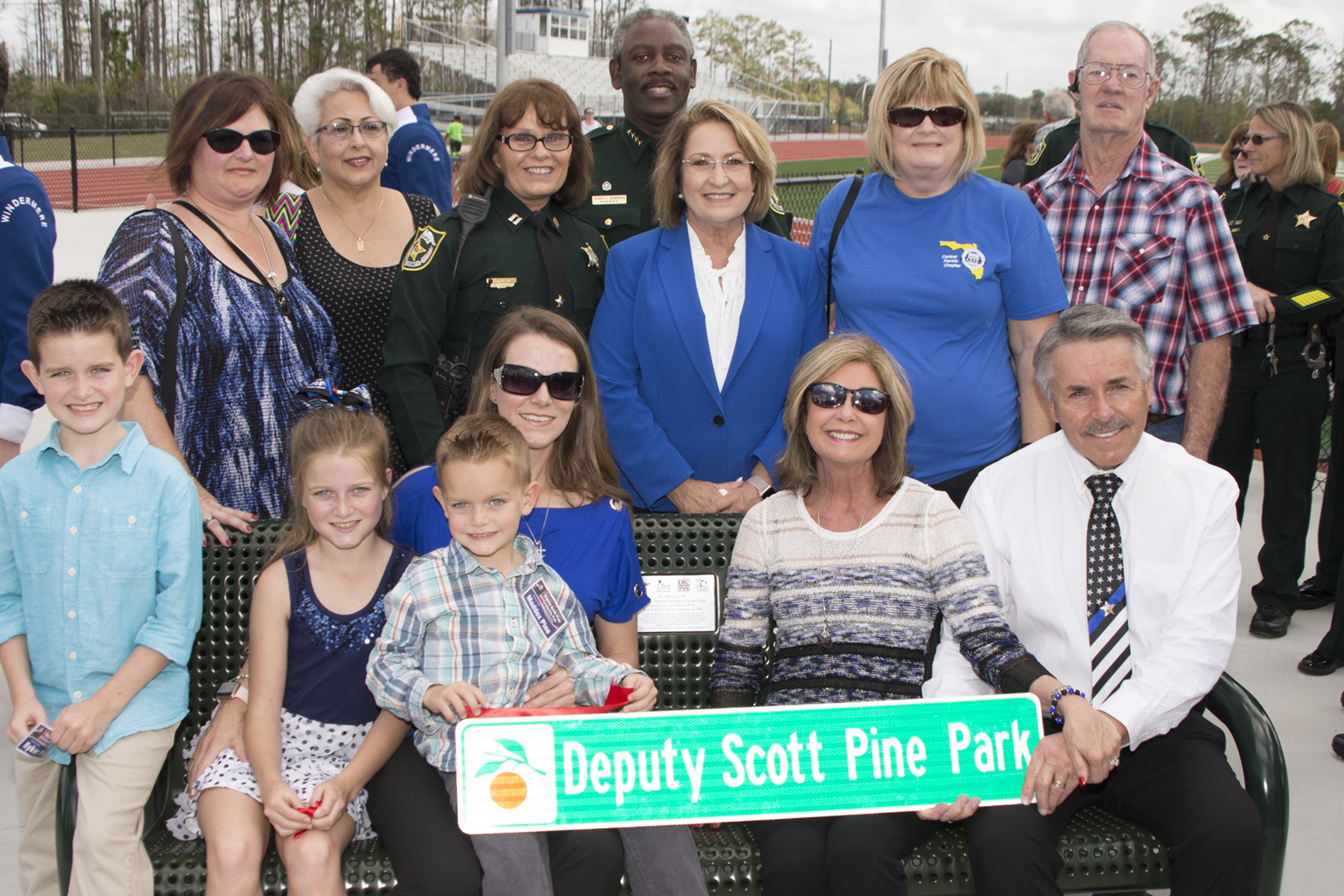 Pine Family and OCFL officials holding park sign