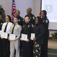 Oficiales de Correccionales del OCFL sostienen sus certificados de reconocimiento