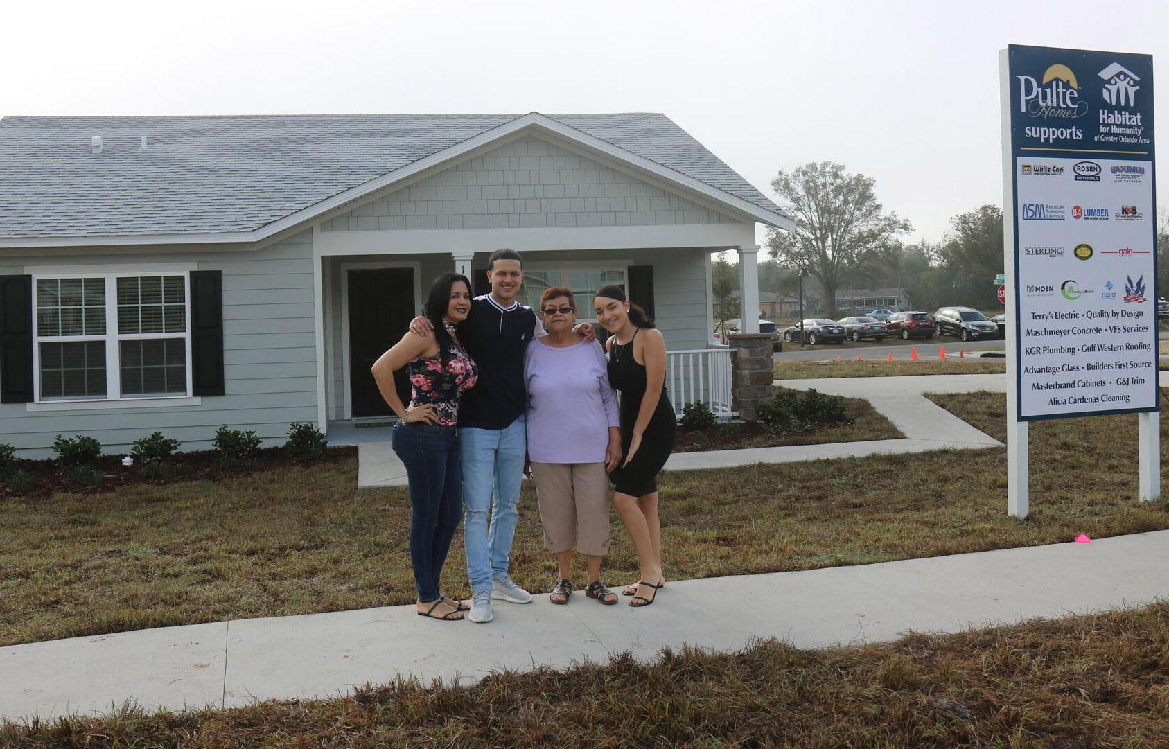 Una familia posando frente a una casa