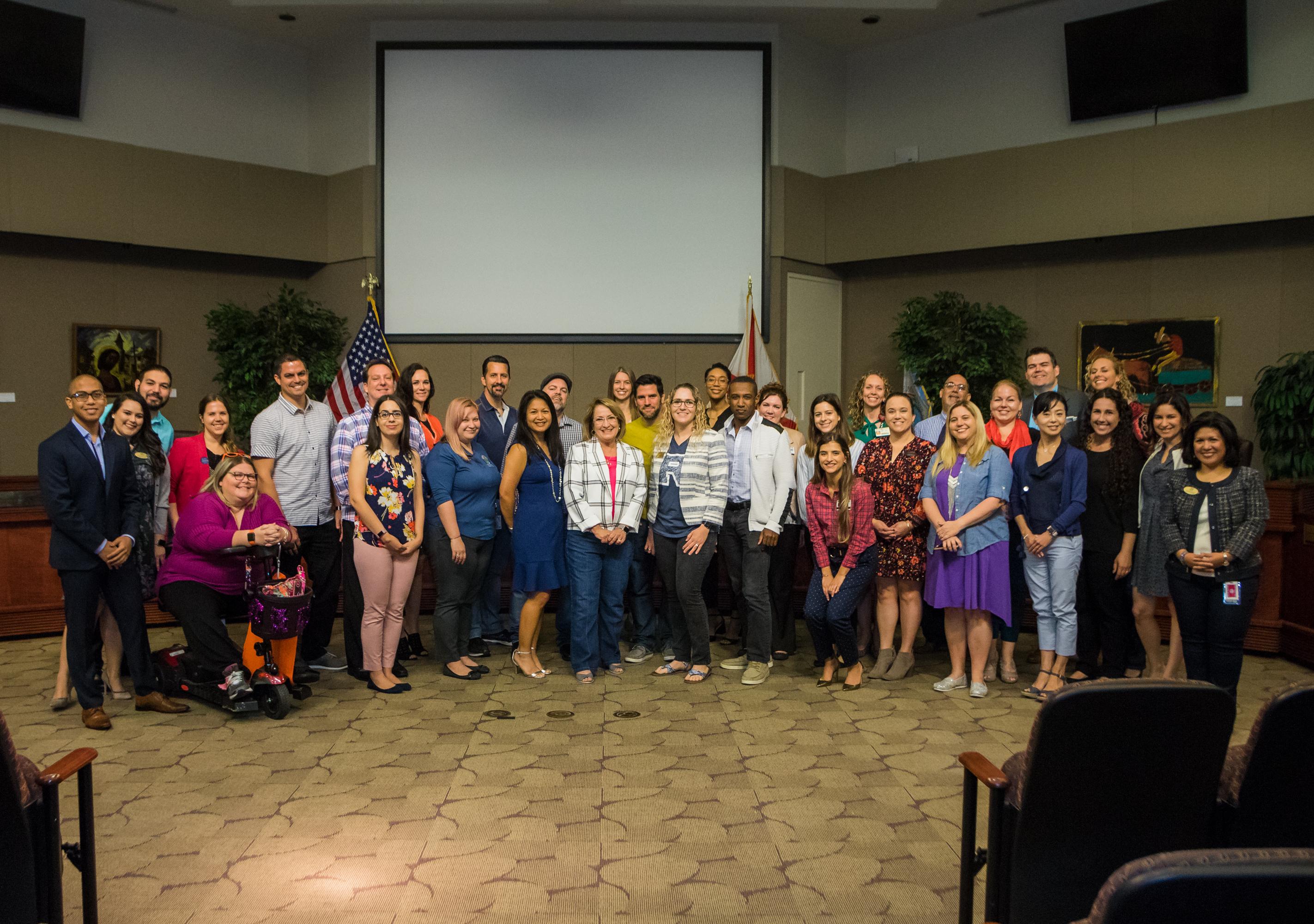 Grupo de alrededor de 30 personas en las Cámaras de la Junta de Comisiones del Condado de Orange