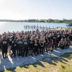 Large group of runners posing by a lake