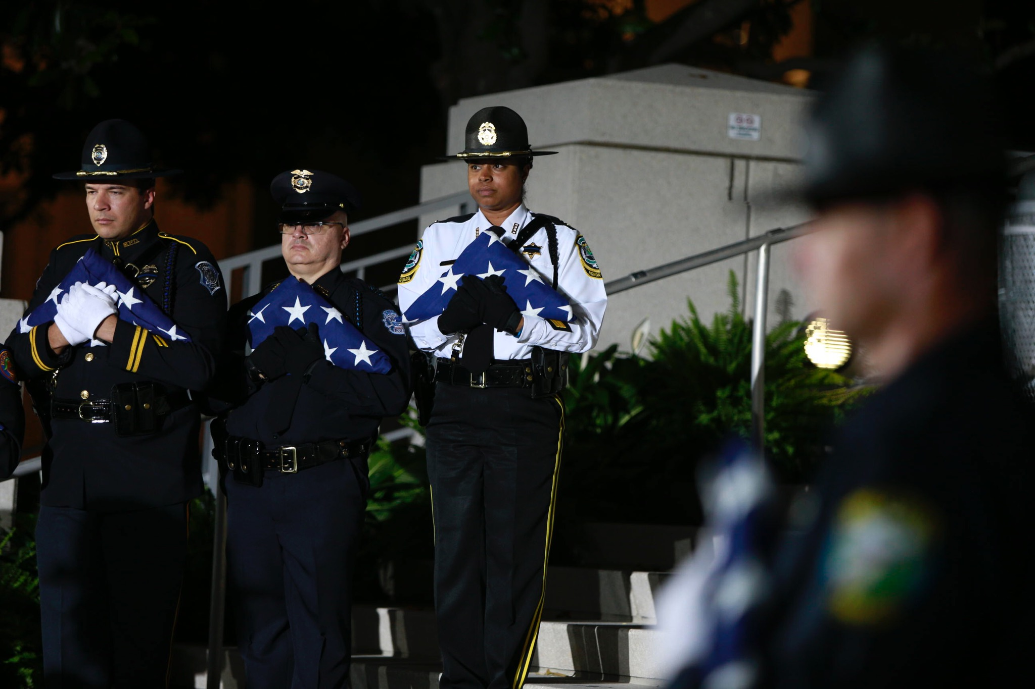 Law enforcement officers on a stage holding triangular folded flags
