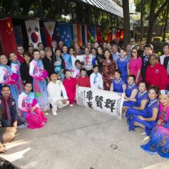 Artistas parados formando un semicírculo con atuendo tradicional para la celebración