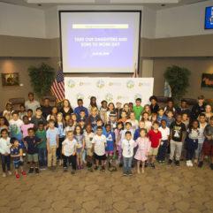 La Alcaldesa Jacobs y decenas de niños posando para una foto en las cámaras de la Junta de Comisionados del Condado