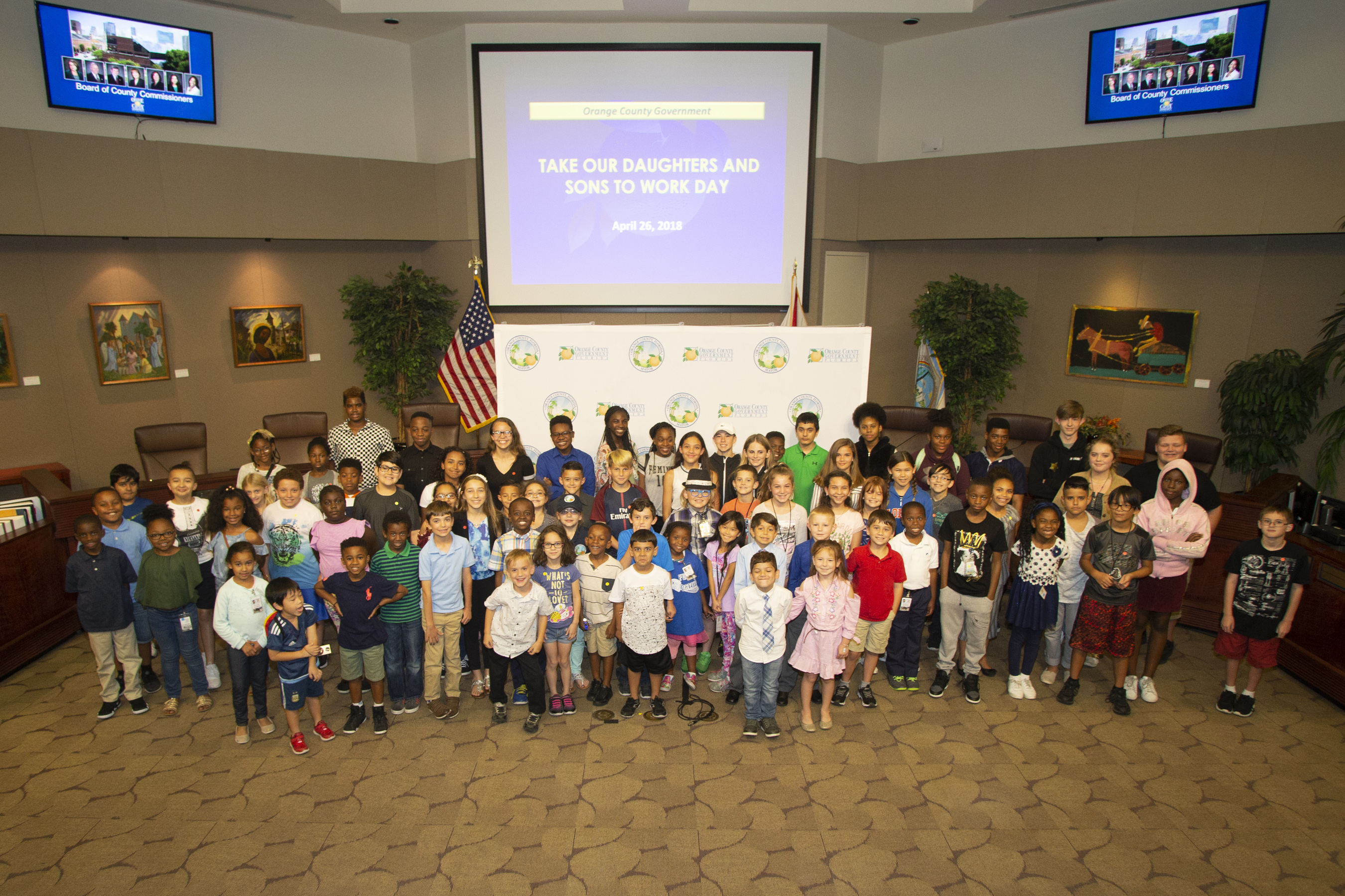 Mayor Jacobs and dozens of children posing for a picture in the Board of County Commissioners chambers