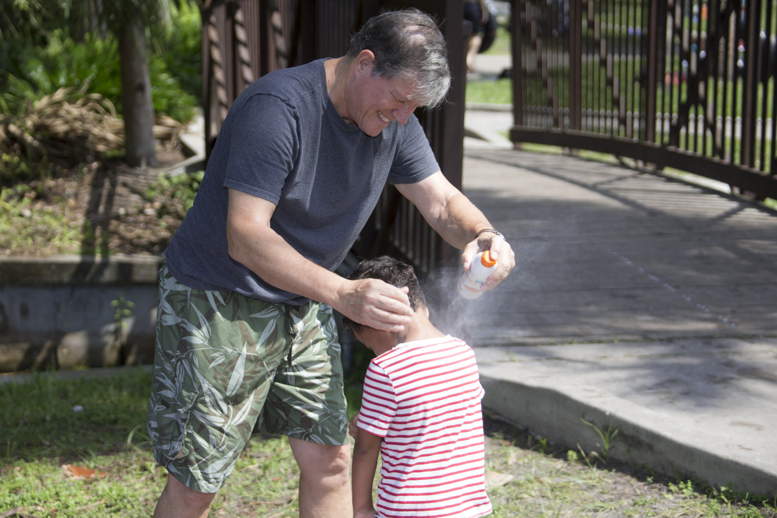A father sprays his son with sunscreen while visiting a park