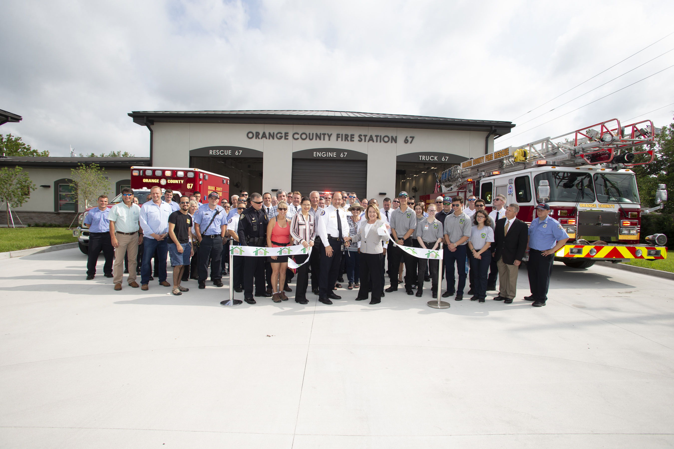 Mayor Jacobs, Fire Chief Drozd and many other people posing for a picture of a ribbon cutting
