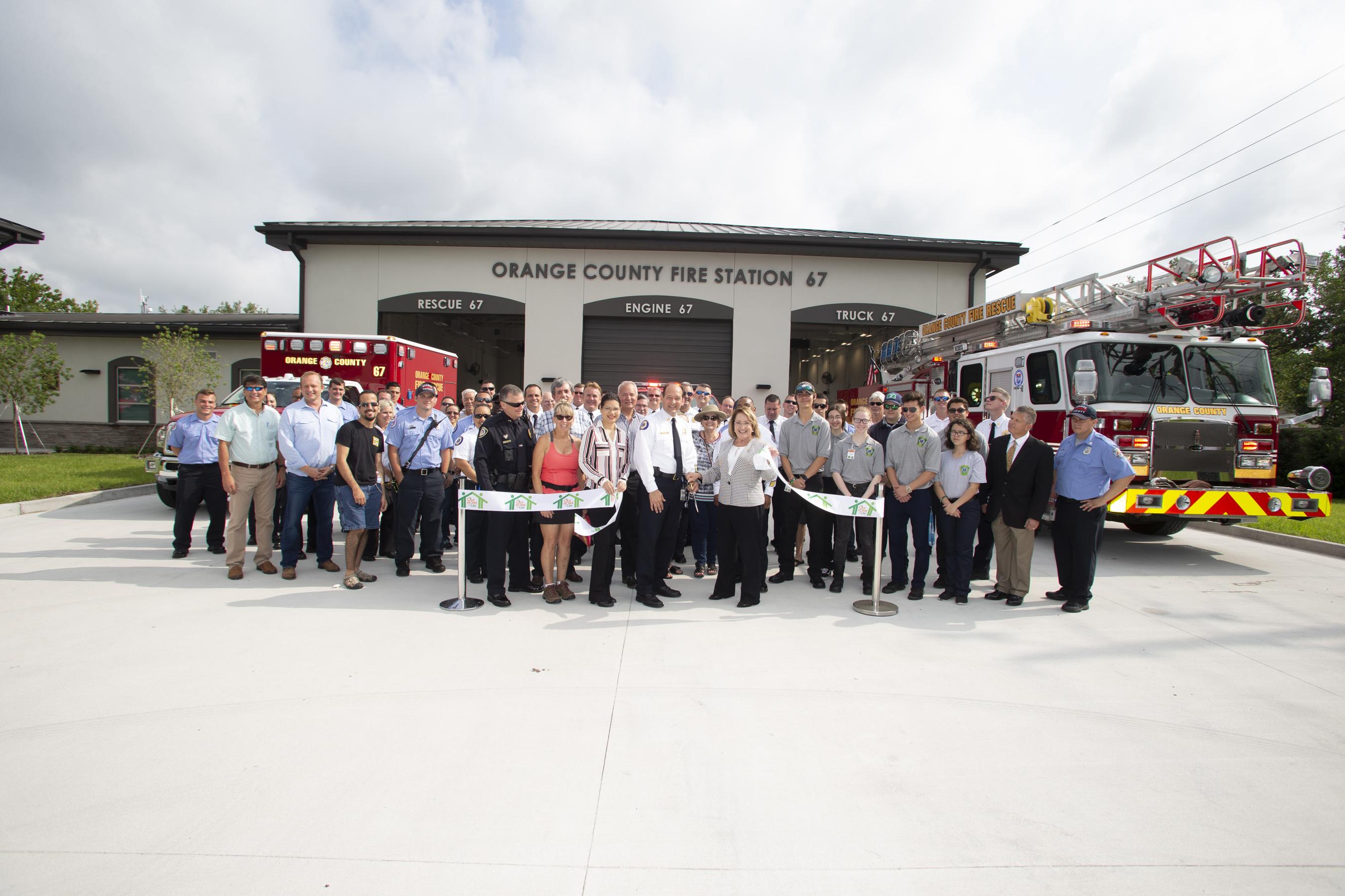 La Alcaldesa Jacobs, el Jefe de Bomberos Drozd y otras personas posan para una foto en la ceremonia de corte de cinta