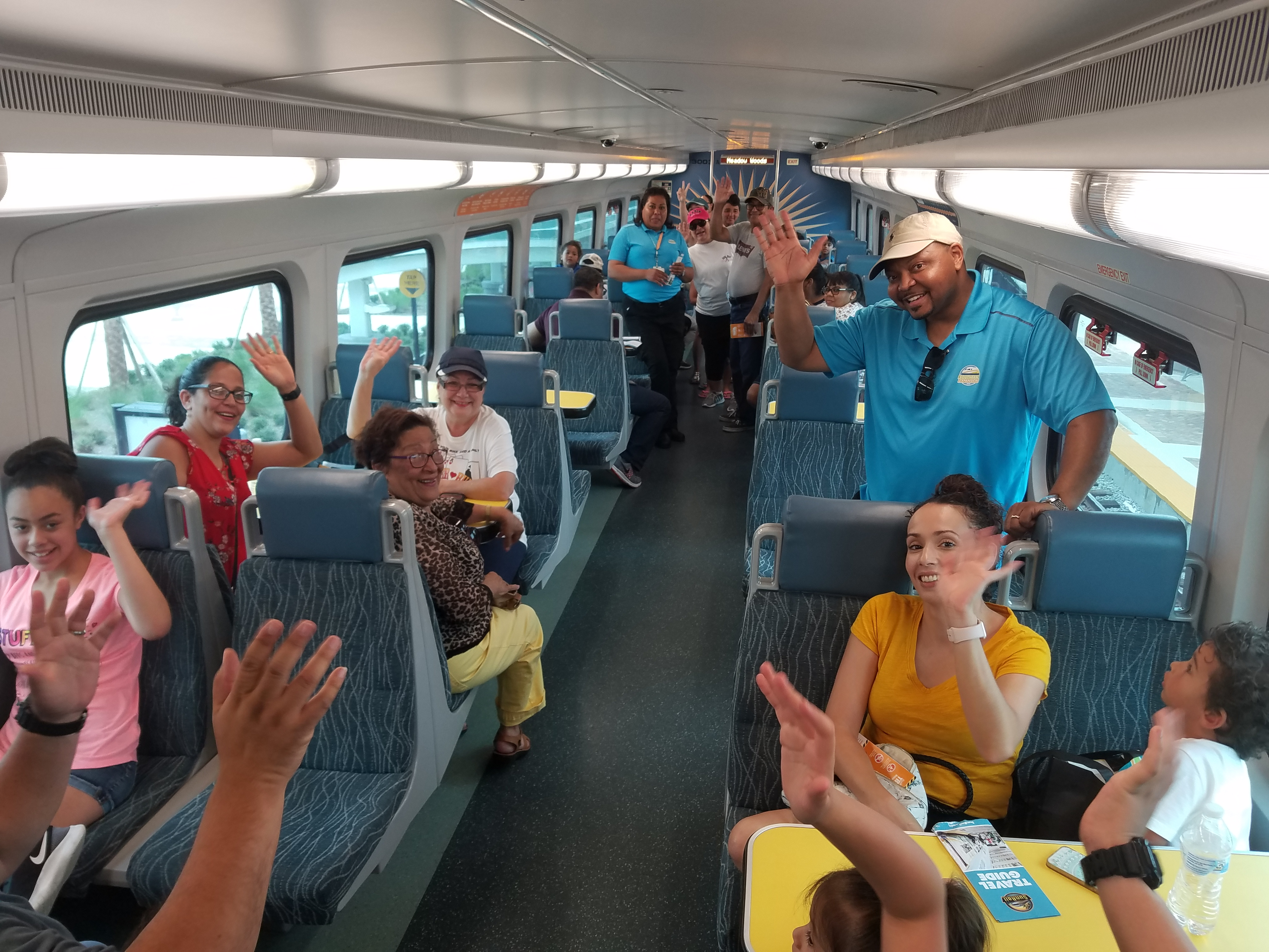 People inside a Sunrail train waving at the camera from their seats