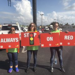 People holding signs that say 'always stop on red'