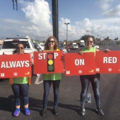 Personas soteniendo carteles que dicen 'deténgase siempre en semáforo en rojo'