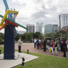 Man speaking to a crowd next to an art sculpture
