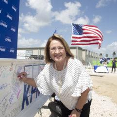 La Alcaldesa Jacobs sonríe mientras firma un banner