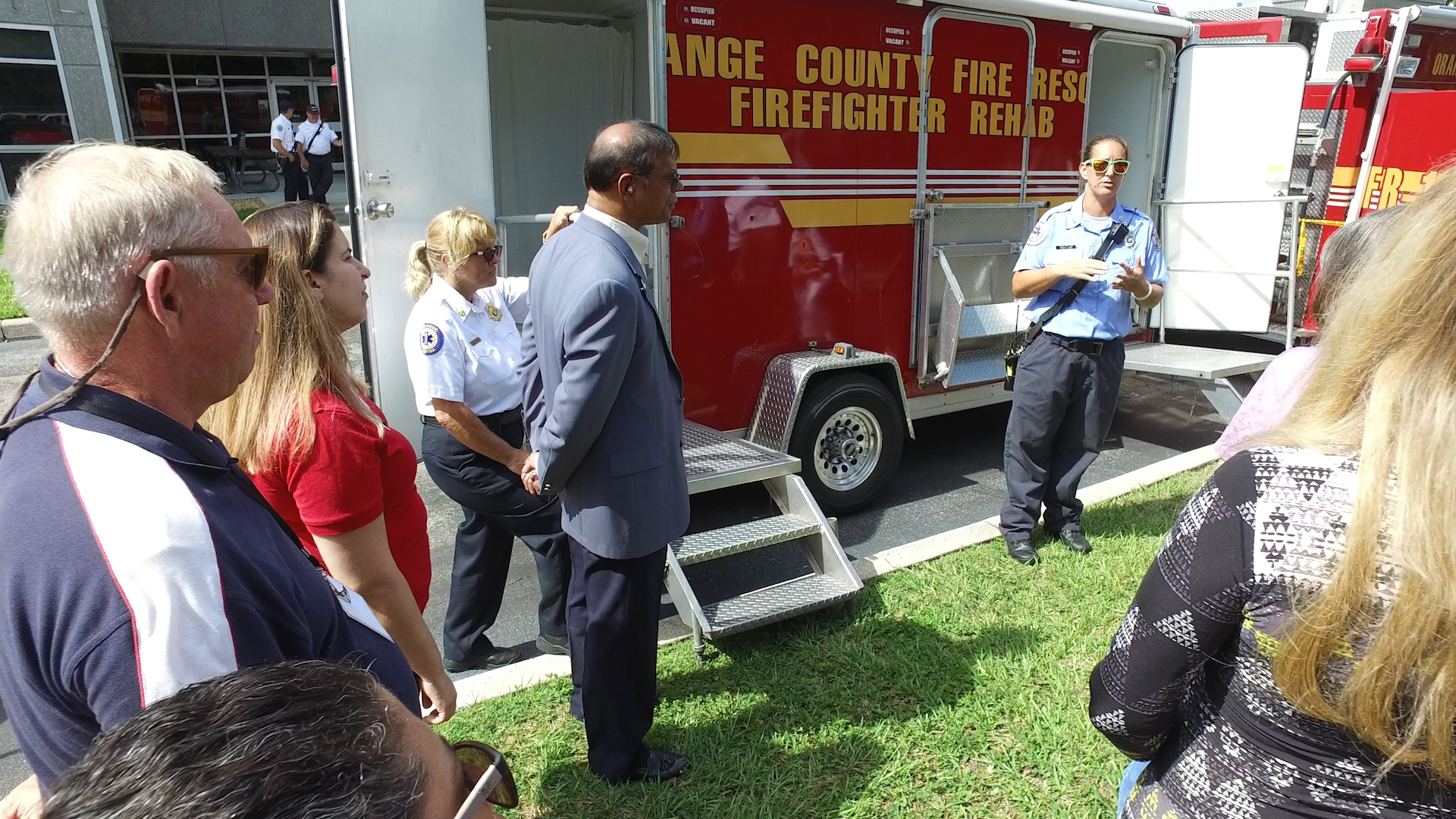 People standing next to a fire truck, listening to a first responder lecture