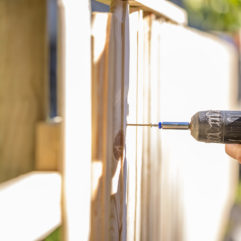 Person holding a drill, drilling into a wooden fence