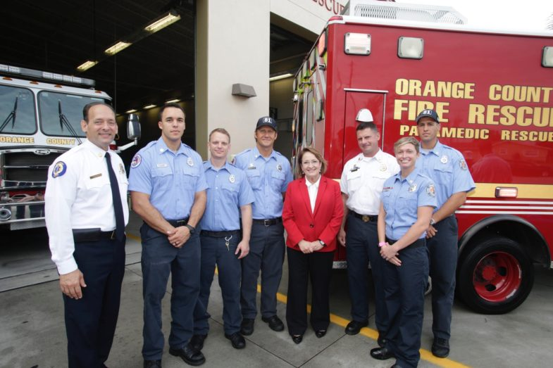 Mayor Jacobs, Chief Drozd, and some first responders stand for a picture at a fire station