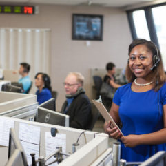 Woman in a 311 call center smiling while others work at their desks