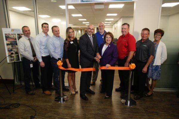 La Alcaldesa Teresa Jacobs y empleados del Condado de Orange posan para la foto en el corte de cinta