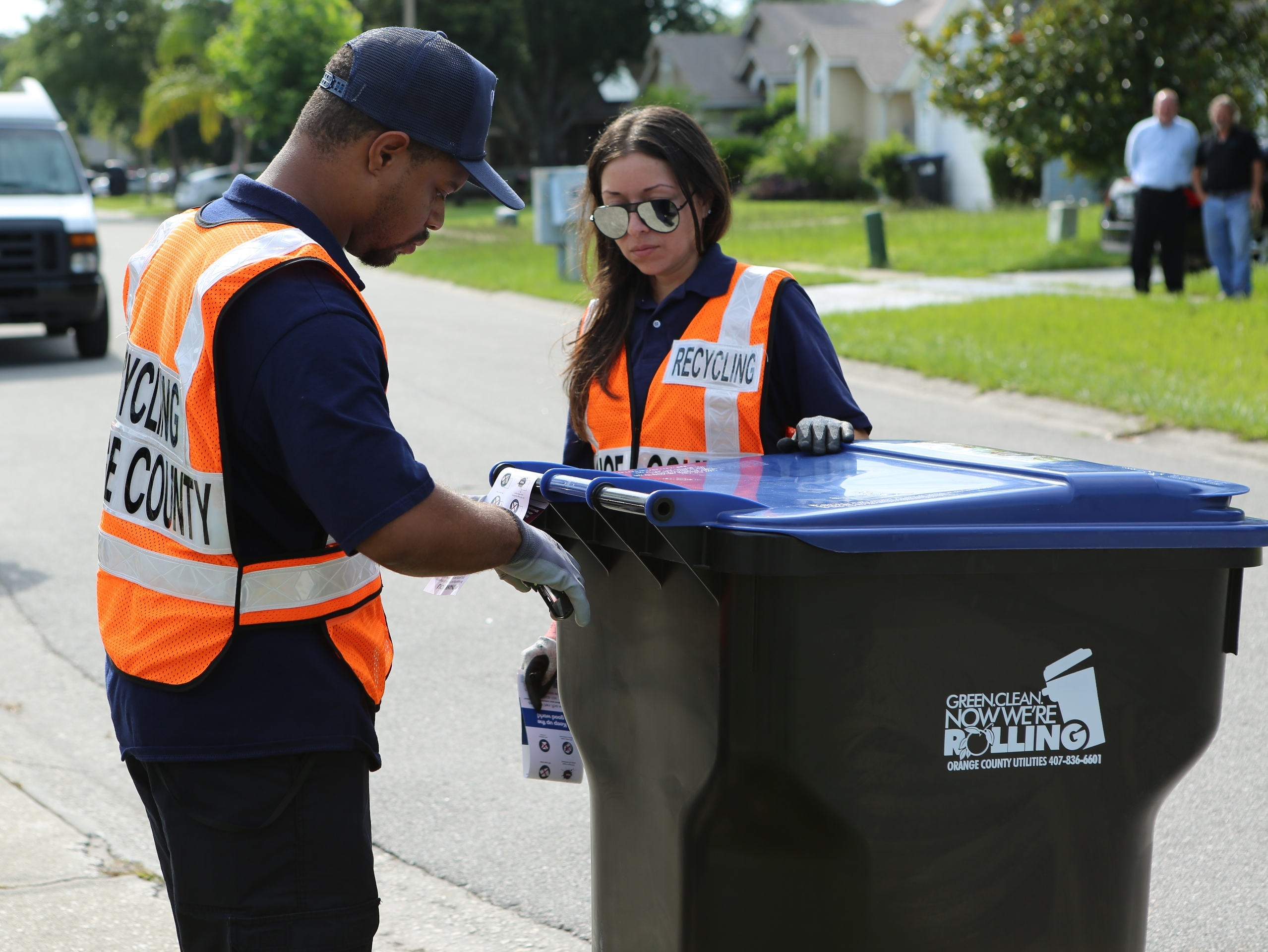 Two employees placing a tag on a recycling bin on the street