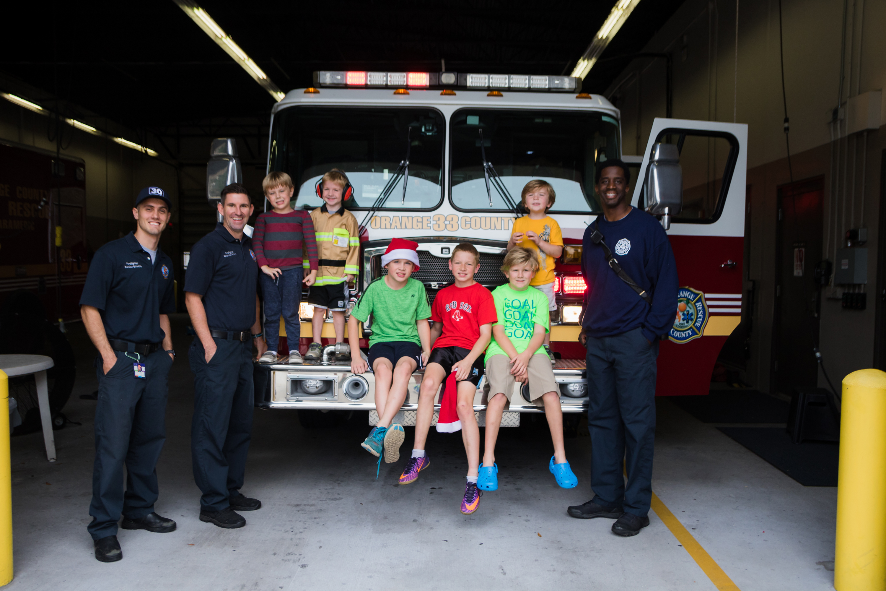 Children and firefighters standing in front of a fire truck