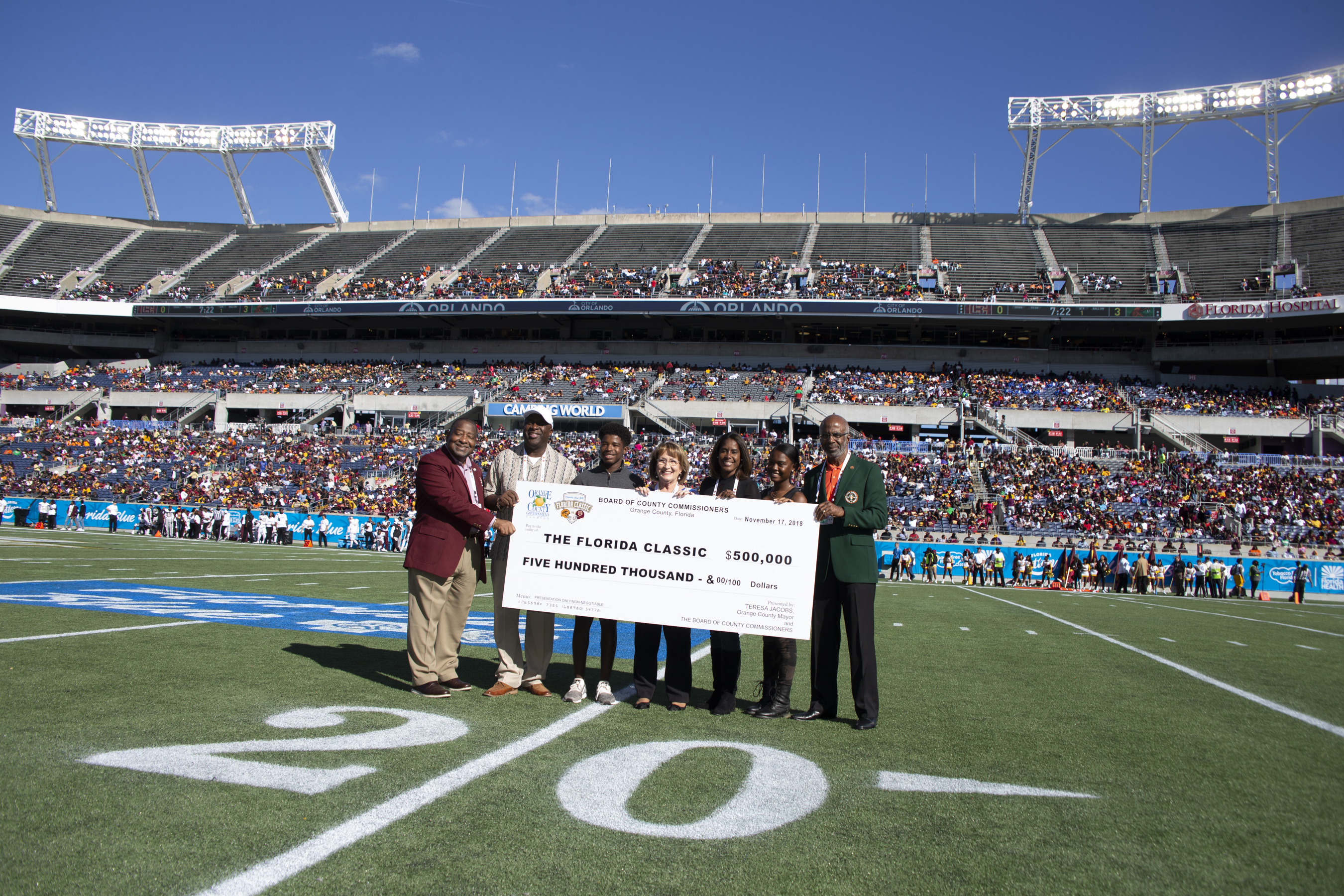 Mayor Jacobs and a small group hold a life-size check in the middle of a football field