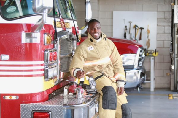 Firefighter Steve O leaning on a fire truck inside the station