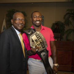 Jesse and Maurice allen holding a trophy belt