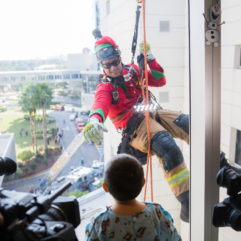 Firefighter rappels outside of children's hospital.