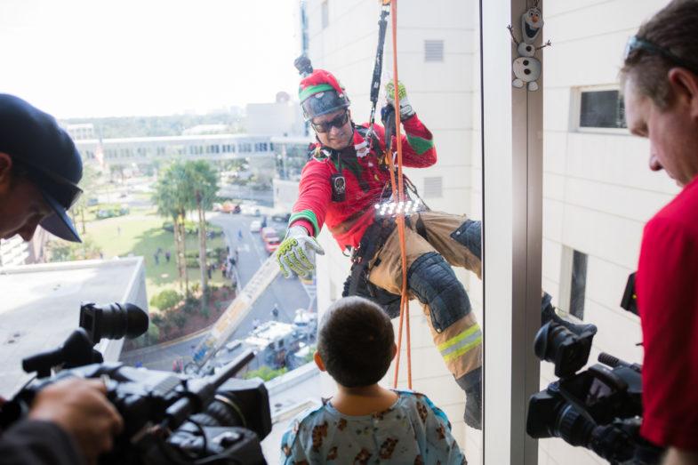 Firefighter rappels outside of children's hospital.