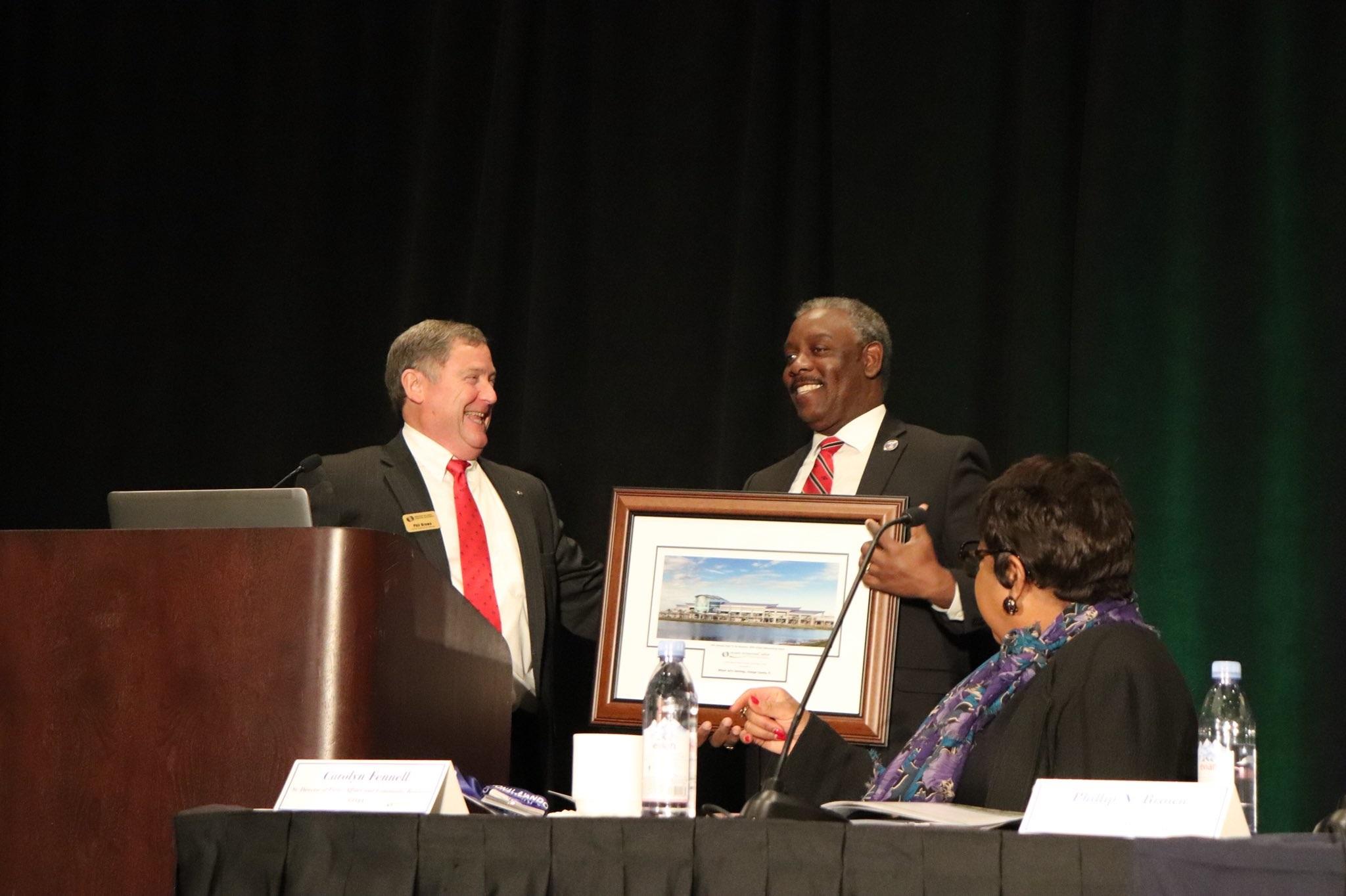 El AlcaldeDemingssostiene una placa con alegría