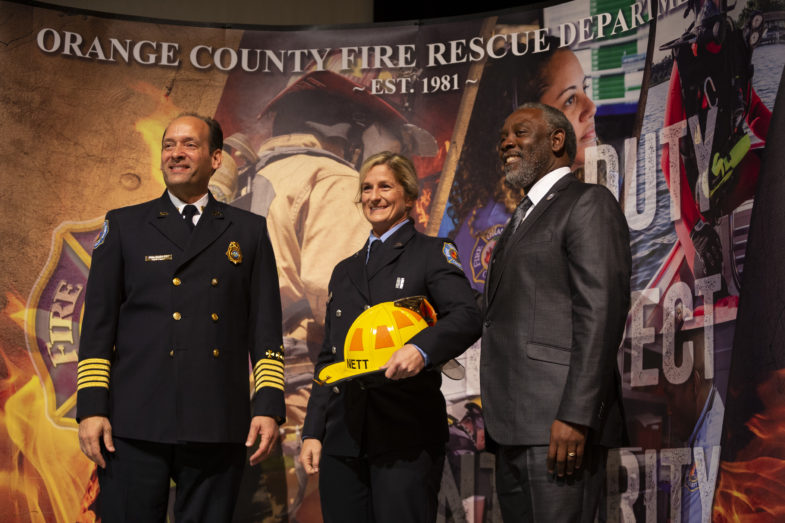 Orange County Fire Rescue Chief Otto Drozd, Orange County Mayor Jerry Demings, and a female graduate from the Fire Rescue academy are standing next to each other posing for a photo.