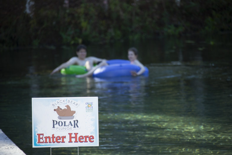 In the foreground there is a sign advertising the polar plunge event, while in the background there are two people on rubber donuts floating in the water.