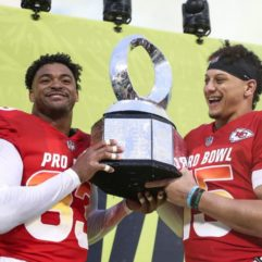 Two NFL players from the Jets football team smiling as they hold the NFL Pro Bowl Championship trophy.