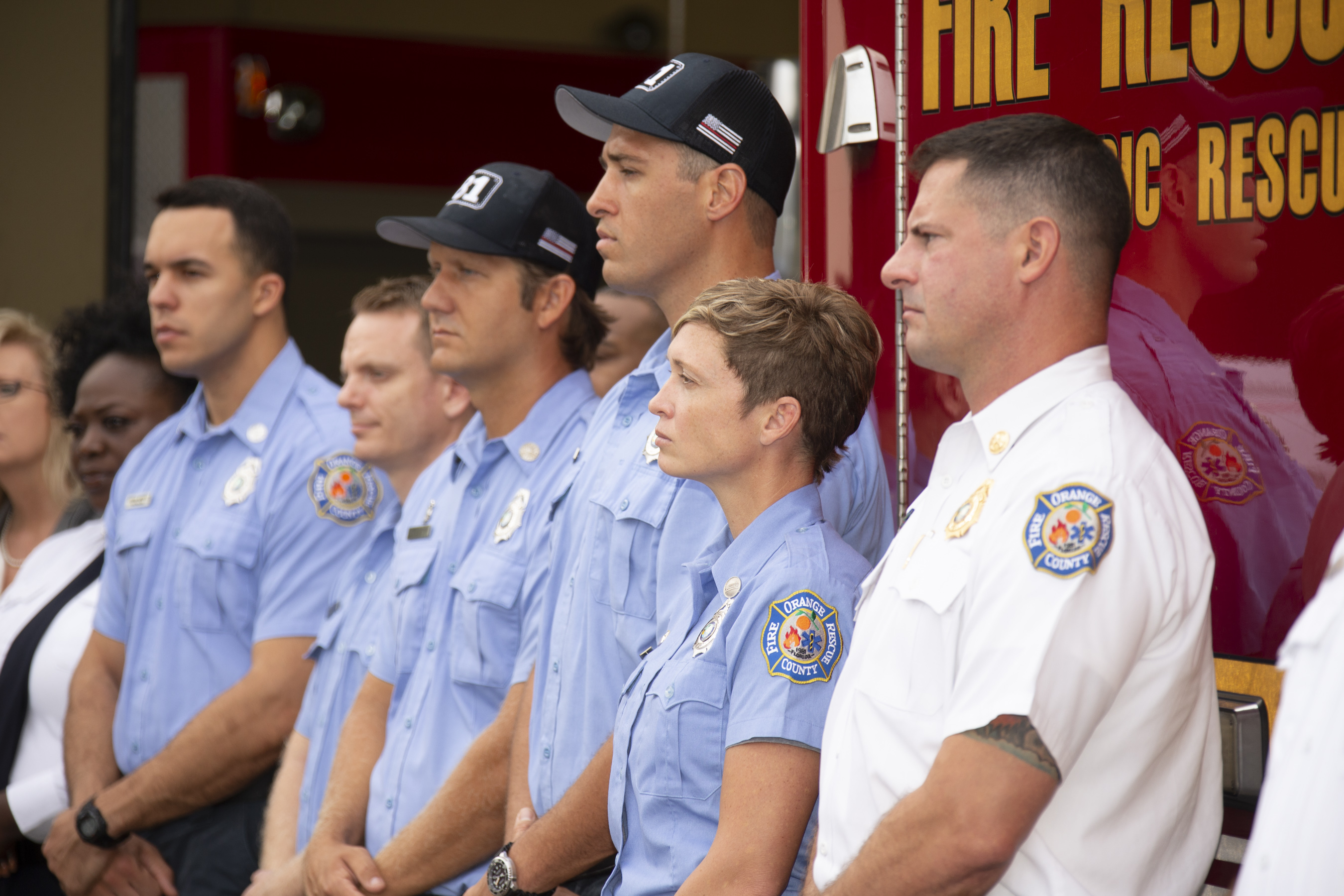 Firefighters standing side by side in front of a fire truck as they listen to a speaker who is not pictured.