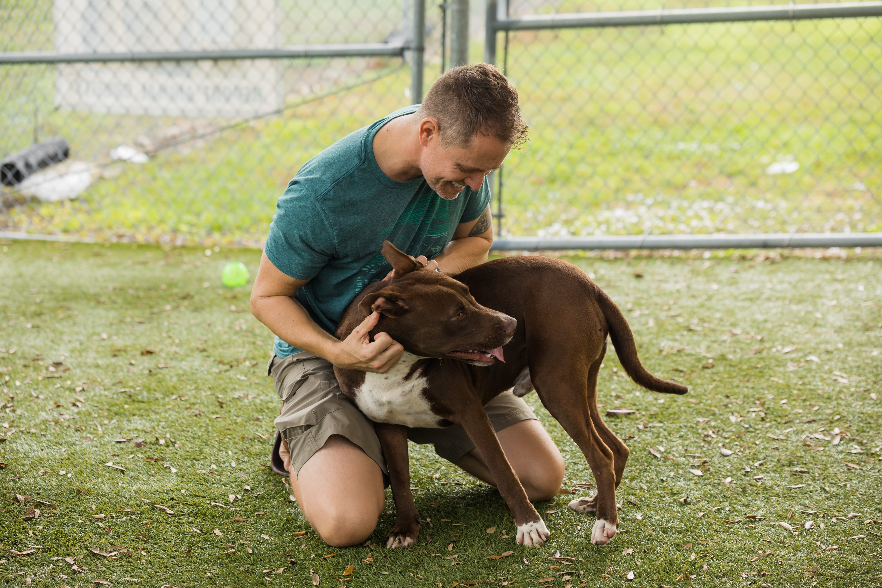 A man kneeling and embracing a large dog while smiling. The two of them are outside in one of Orange County Animal Services' play areas.