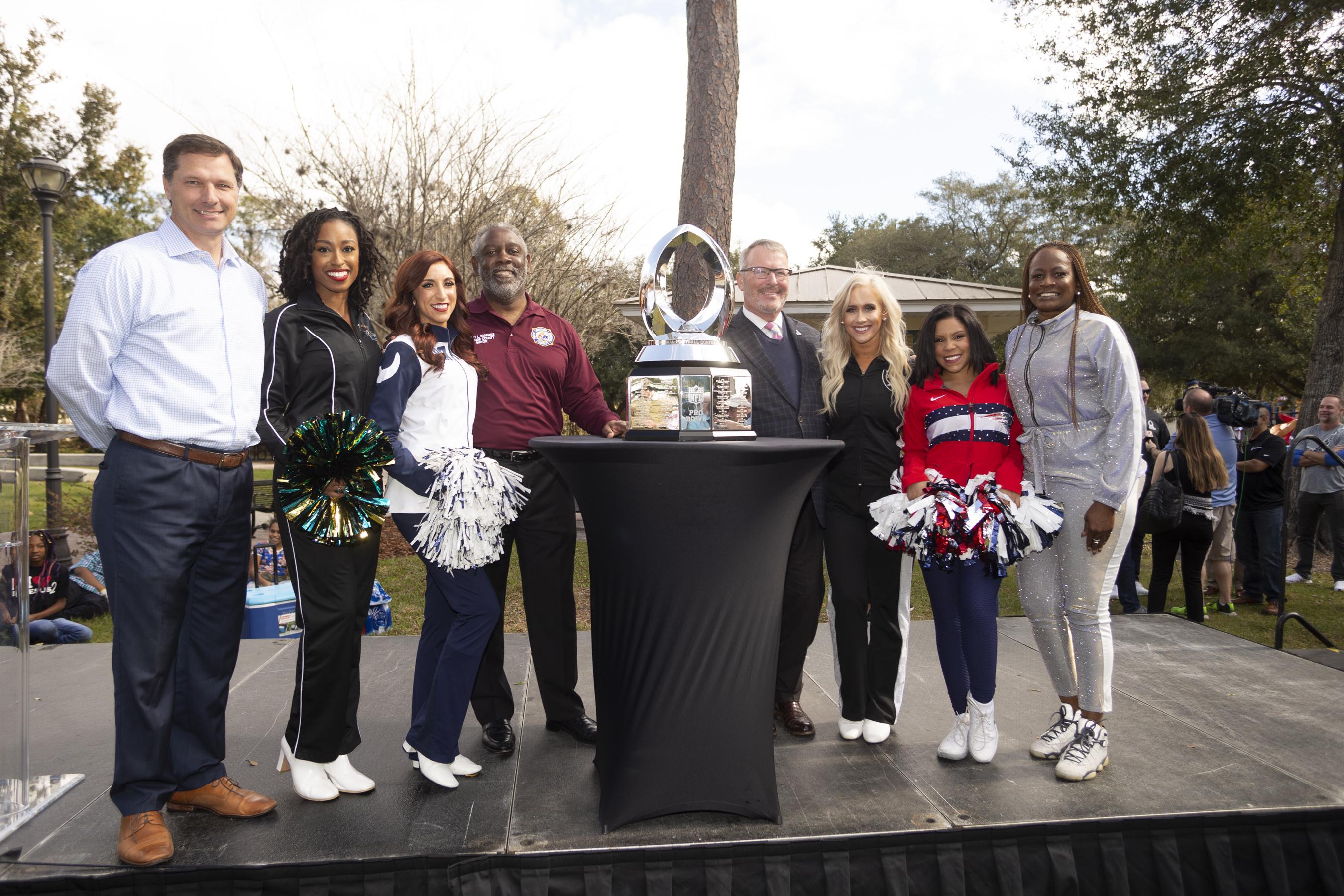 El Alcalde Demings, líderes de la comunidad y representantes de la NFL permanecen de pie en el estrado junto al trofeo del partido del Pro Bowl de la NLF 2019.