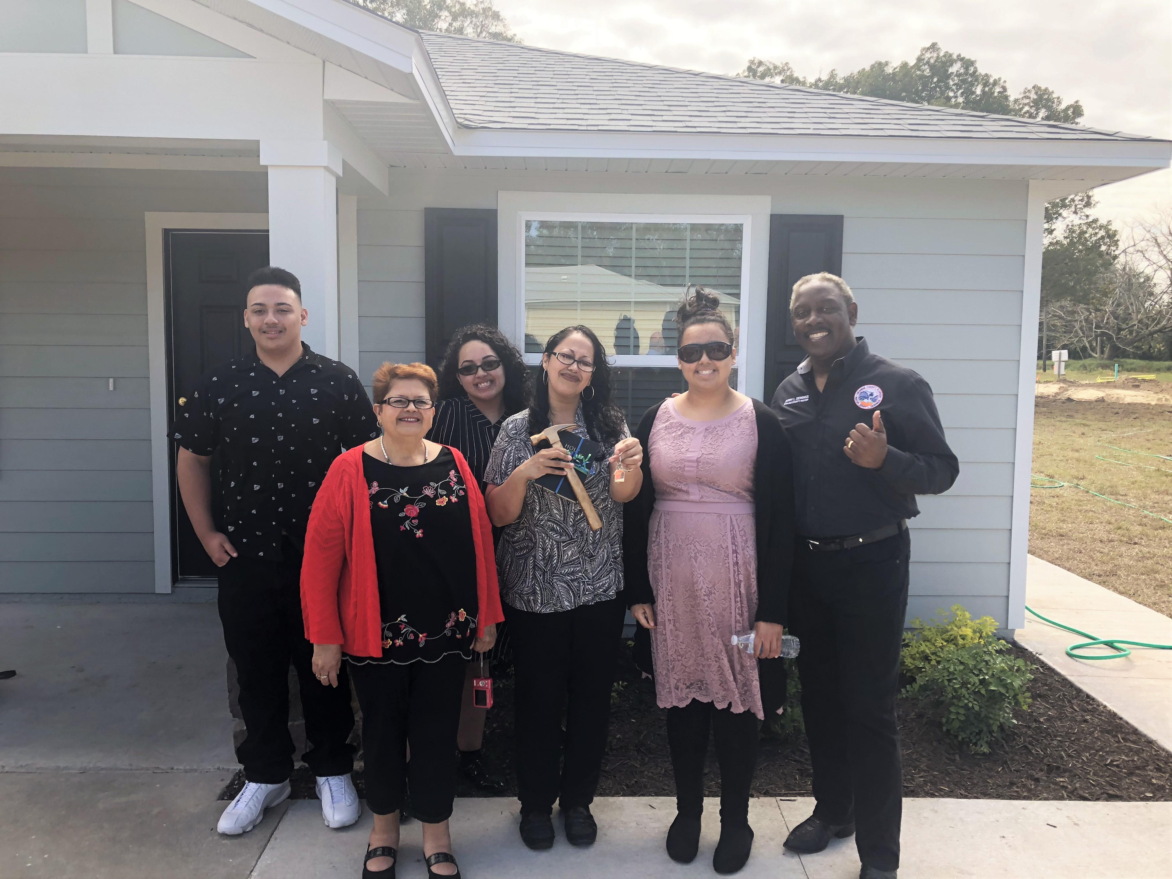 Cinco miembros de una familia parados junto al Alcalde Demings frente a su nueva casa de Habitat for Humanity.