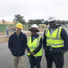 Three Habitat for Humanity employees wearing vests and hard hats pose for a photo. In the background, homes are actively being built.