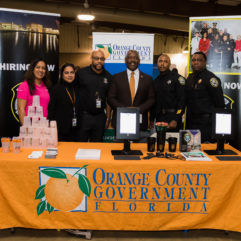 Mayor Demings with Orange County staff standing at the Orange County booth during the Mayor's Job Fair.