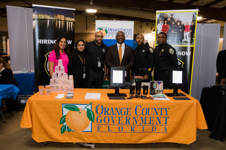 Mayor Demings with Orange County staff standing at the Orange County booth during the Mayor's Job Fair.