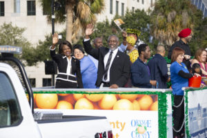 Mayor Demings and his wife Congresswoman Valdez Demings on the Orange County float, waving towards the parade audience.