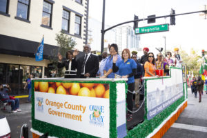 Mayor Demings, his wife, and two Orange County Commissioners are joined by dozens of volunteer employees on the Orange County Float as they pass Magnolia Street in Downtown Orlando.